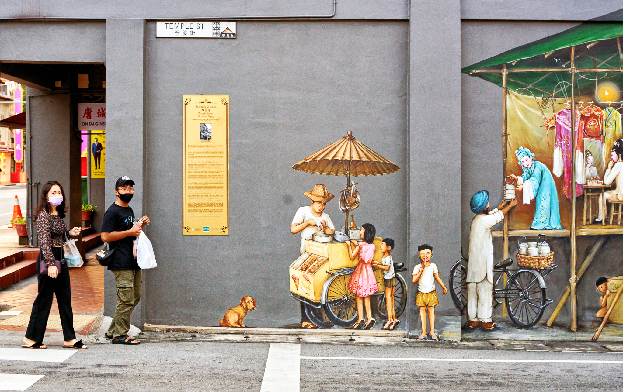A couple passing by the wall mural, Temple Street, China Town, Singapore