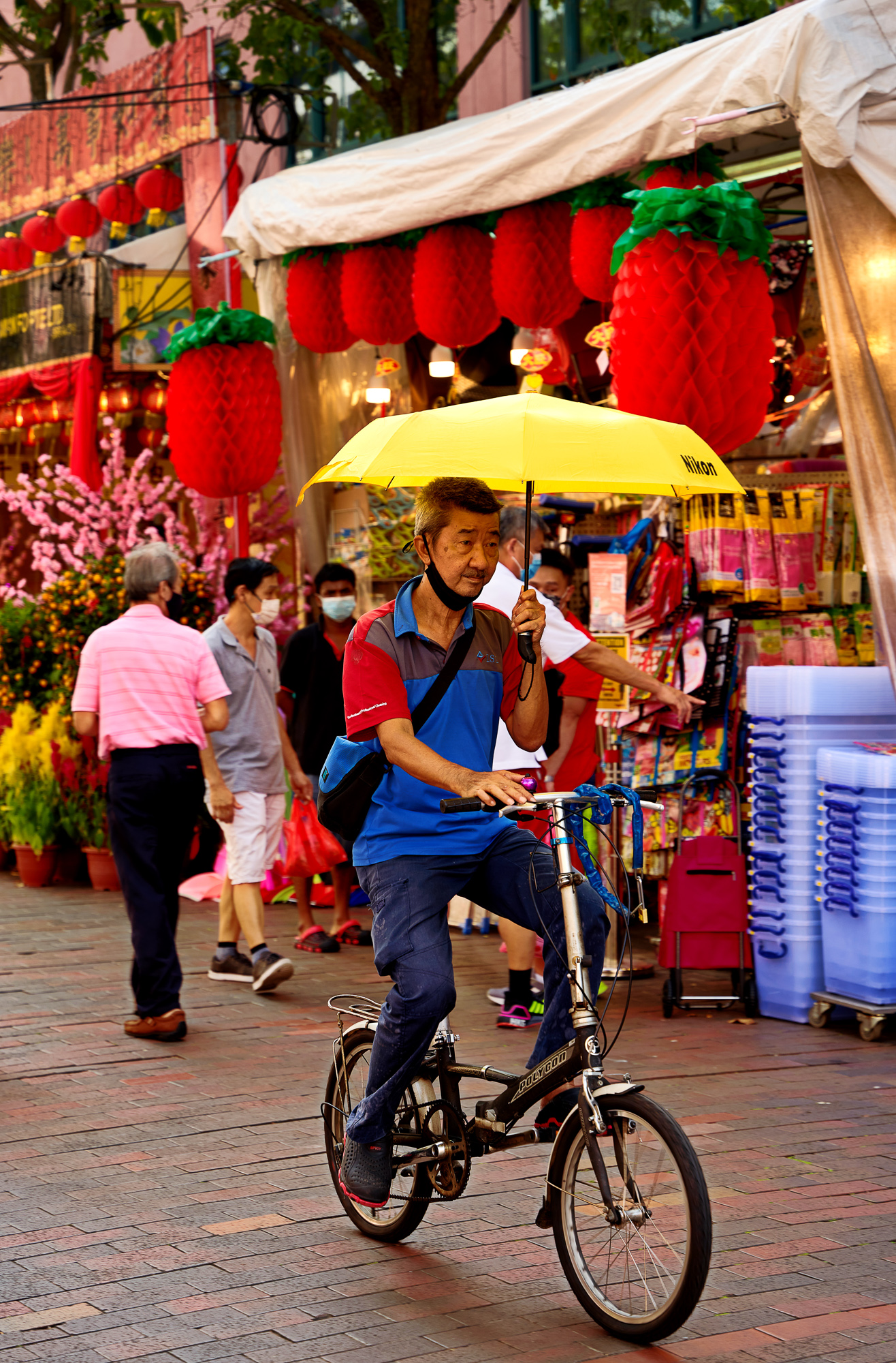 A cyclist with a colorful umbrella, Waterloo Street, Bugis, Singapore