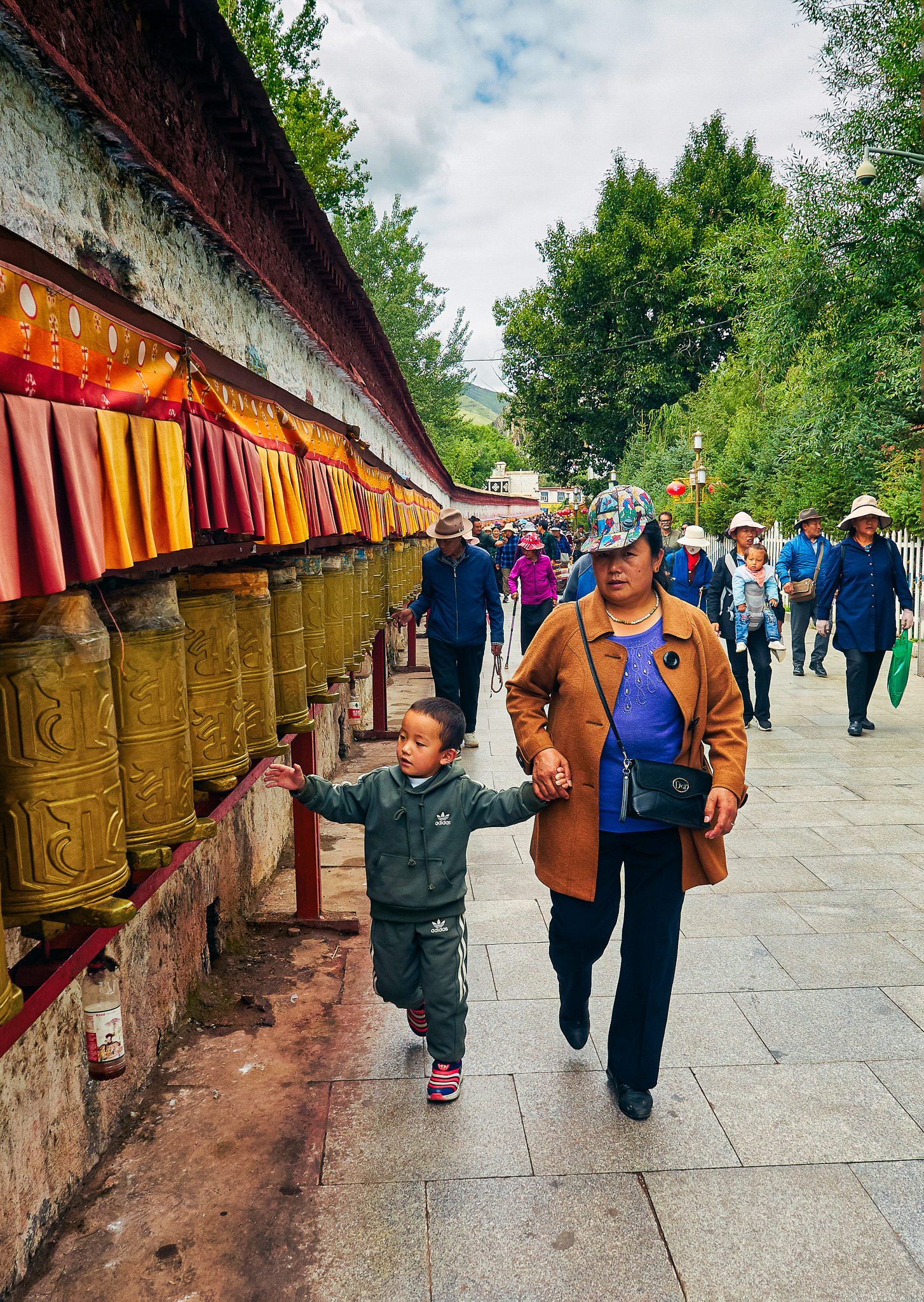 A Tibetan mother and son rolling the prayer wheels while circumambulating the sacred path, Lingkhor, outside the Potala Palace, Lhasa, Tibet