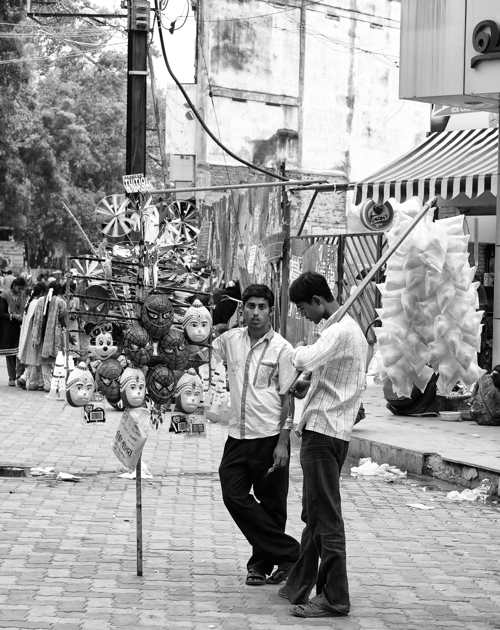 Young street vendors selling toys, masks and cotton candies. Madurai, Tamil Nadu, India