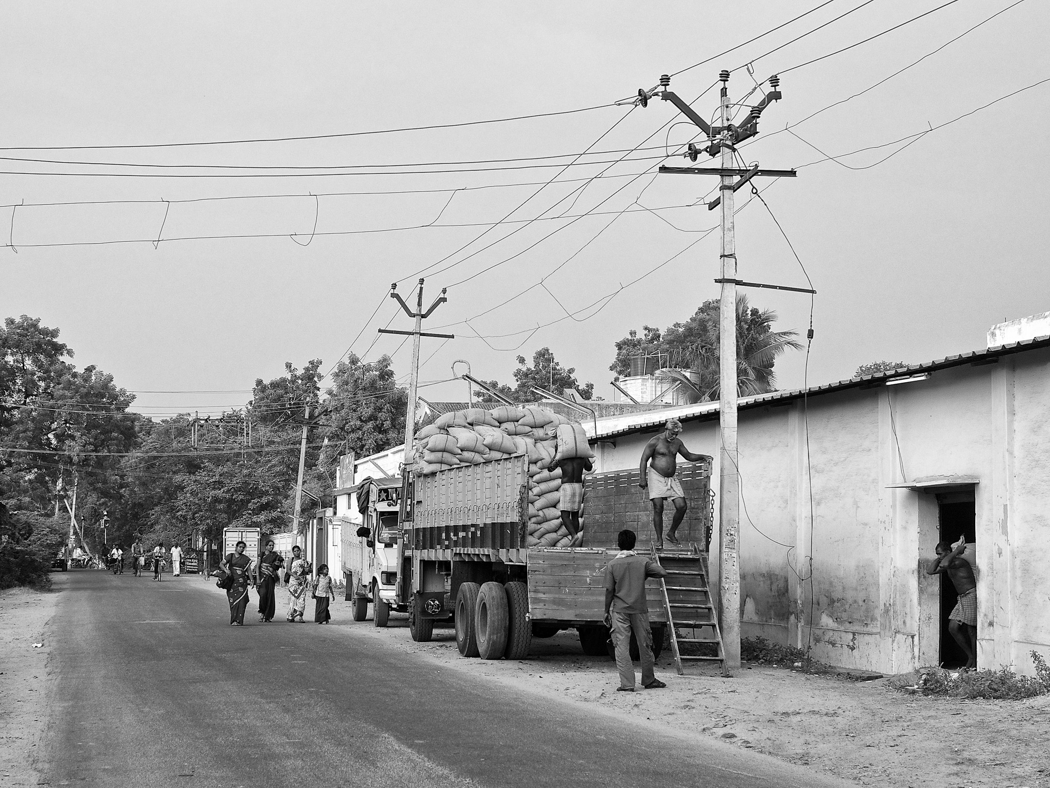 Loading men at work by the road side and teachers returning home, Virudhunagar, Tamil Nadu, India