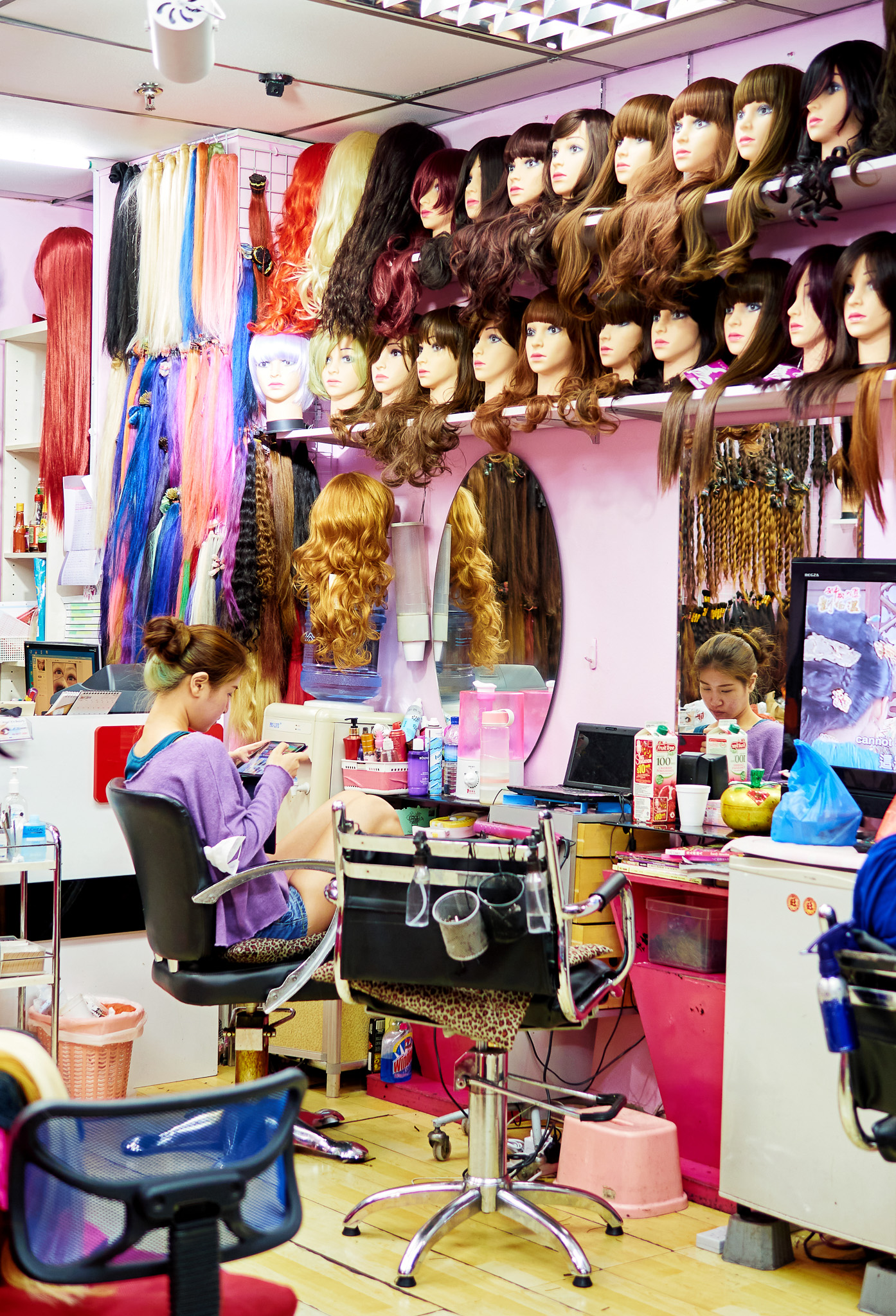 A young girl awaiting in the salon, filled with colorful hair wigs, Paya Lebar, Singapore