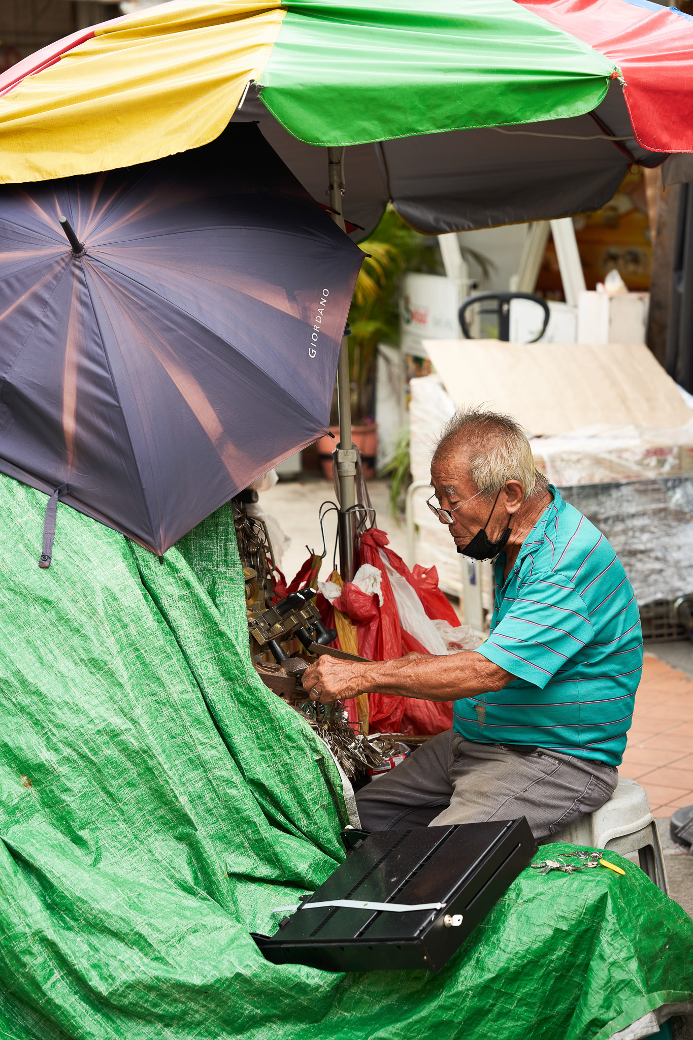 A senior locksmith at work by the roadside, Rowell Road, Little India, Singapore