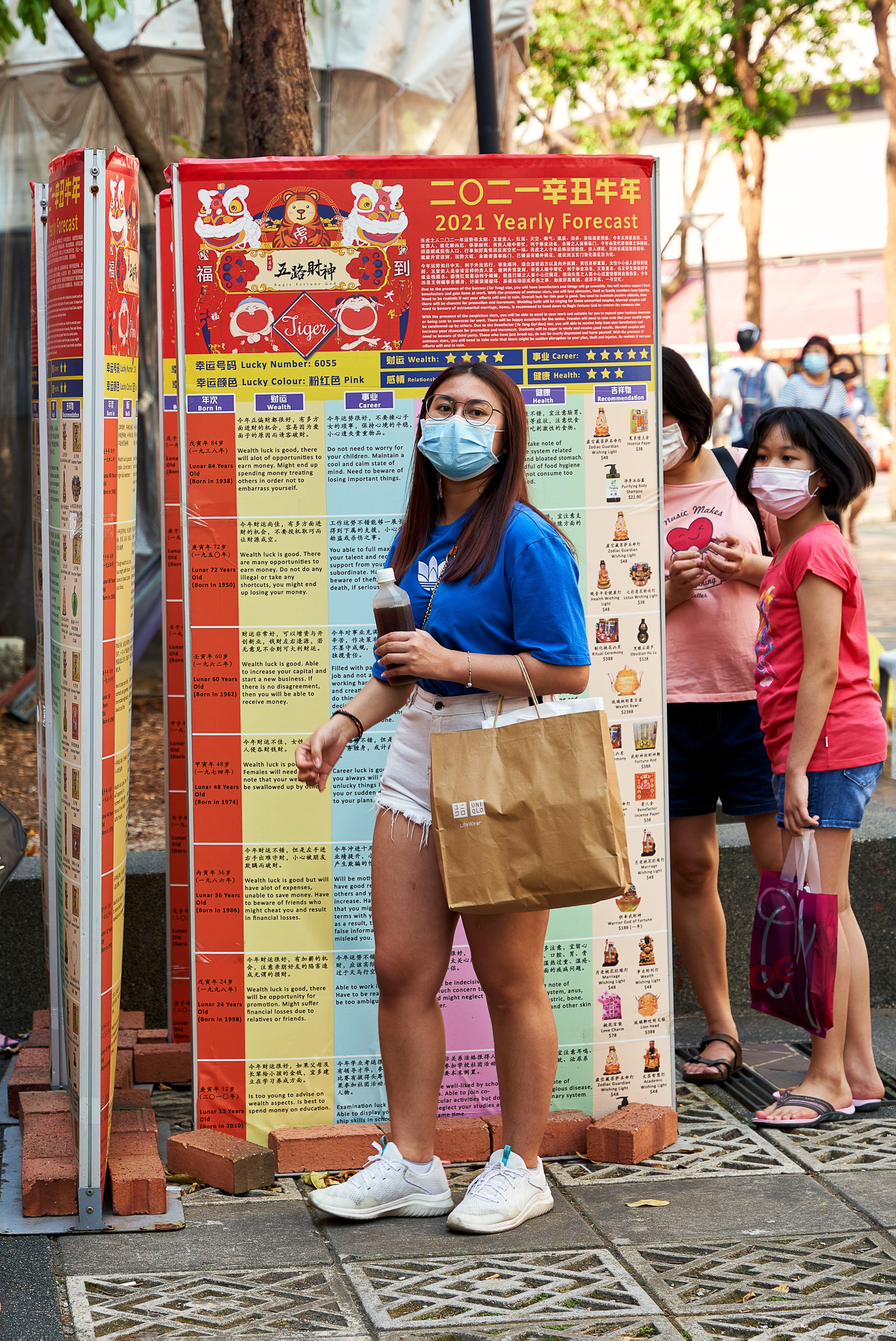 People checking out their yearly forecast for their respective zodiac for the Lunar New Year, Bugis, Singapore
