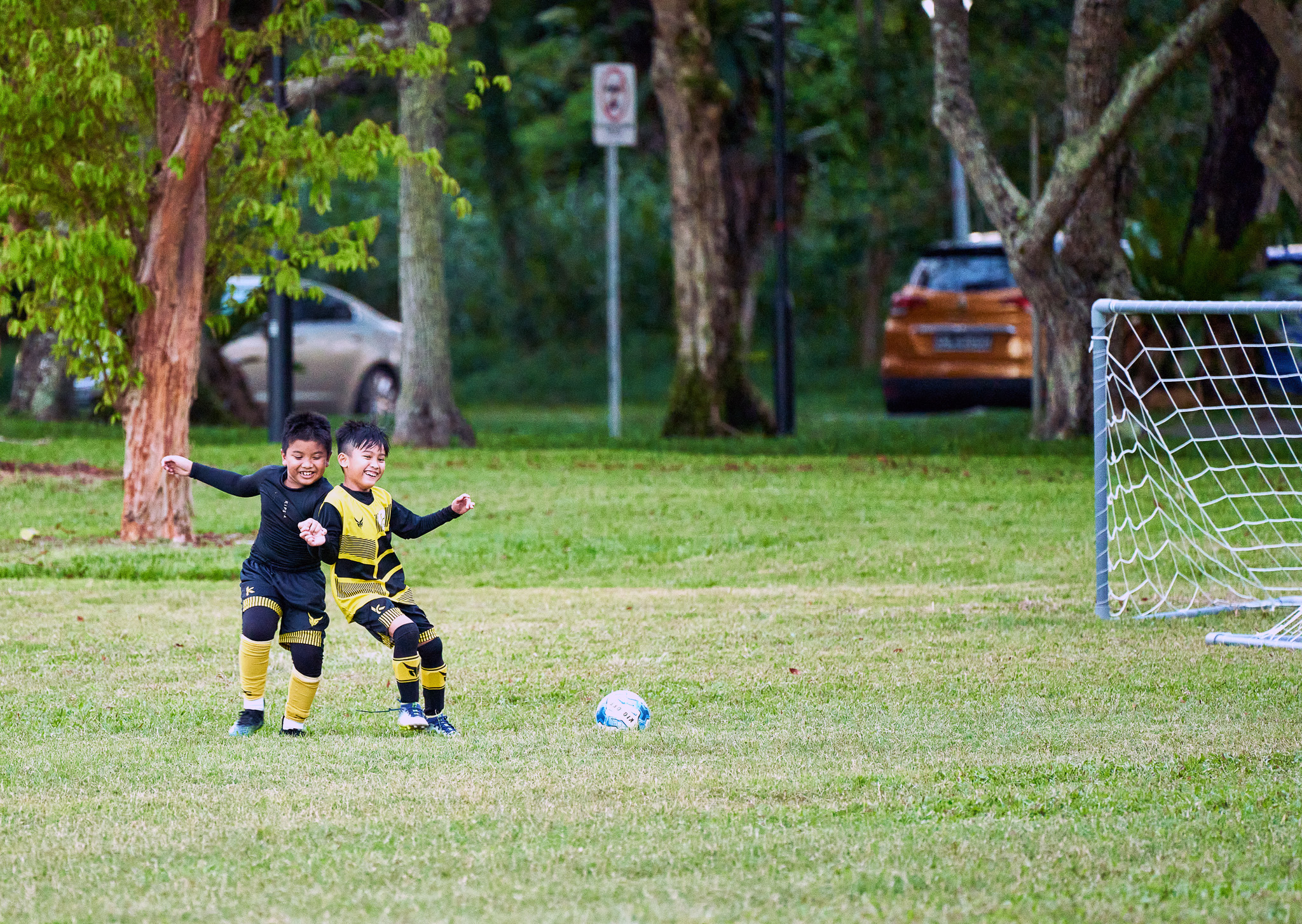 Young kids in a friendly tussle at their Sunday evening soccer, Pasir Ris Park, Singapore
