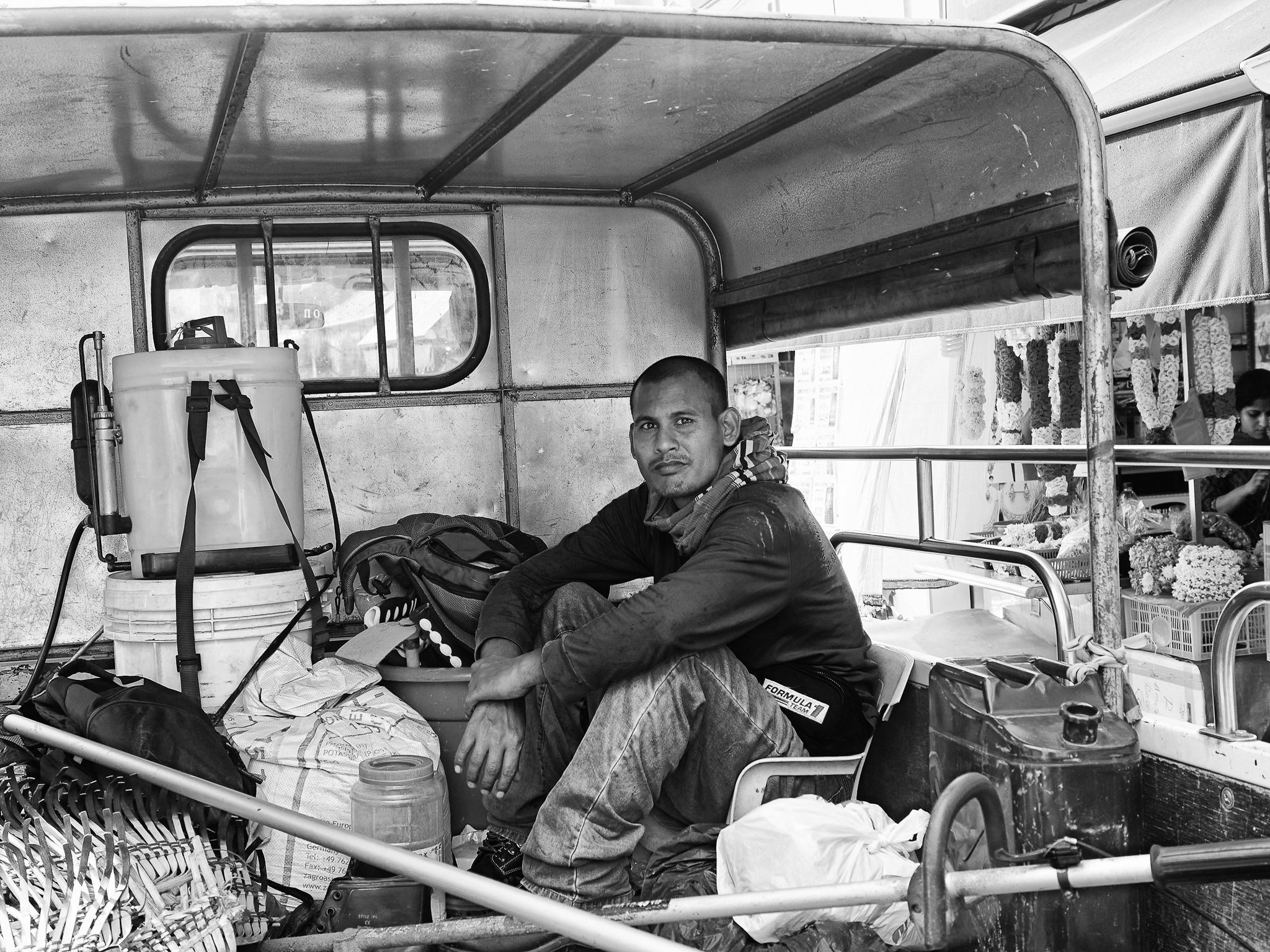 An immigrant worker in the back up of the pickup lorry amongst the construction materials, Little India, Singapore