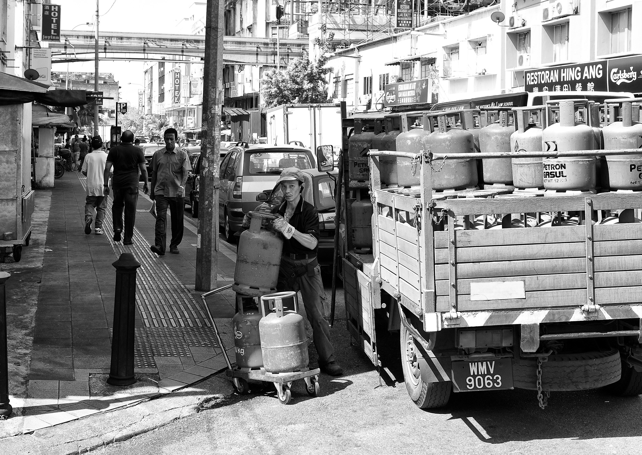 Gas delivery man offloading a few cylinders into his trolley. Brickfields, Kuala Lumpur, Malaysia