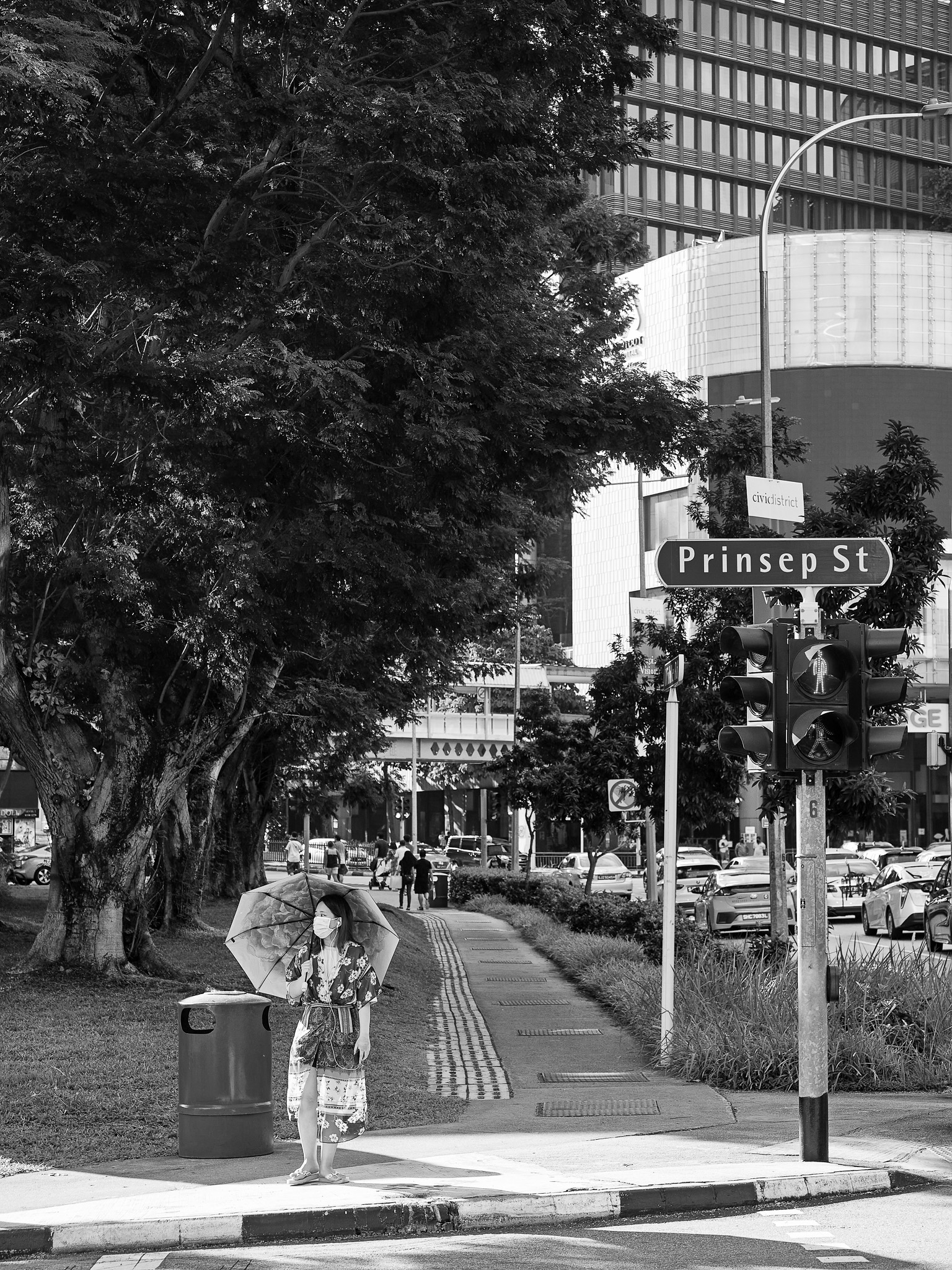 A woman with an umbrella waiting to cross the road, Prinsep Street, Bugis, Singapore