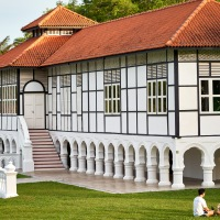 A family spending their evening in front of the oldest surviving black-and-white bungalow built in 1898, Gallop Extension at Singapore Botanic Gardens, Singapore