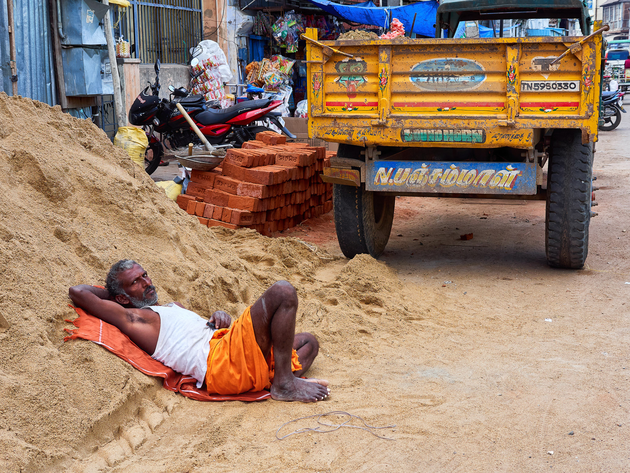 A man resting on a heap of sand at the roadside construction, Madurai, Tamil Nadu, India
