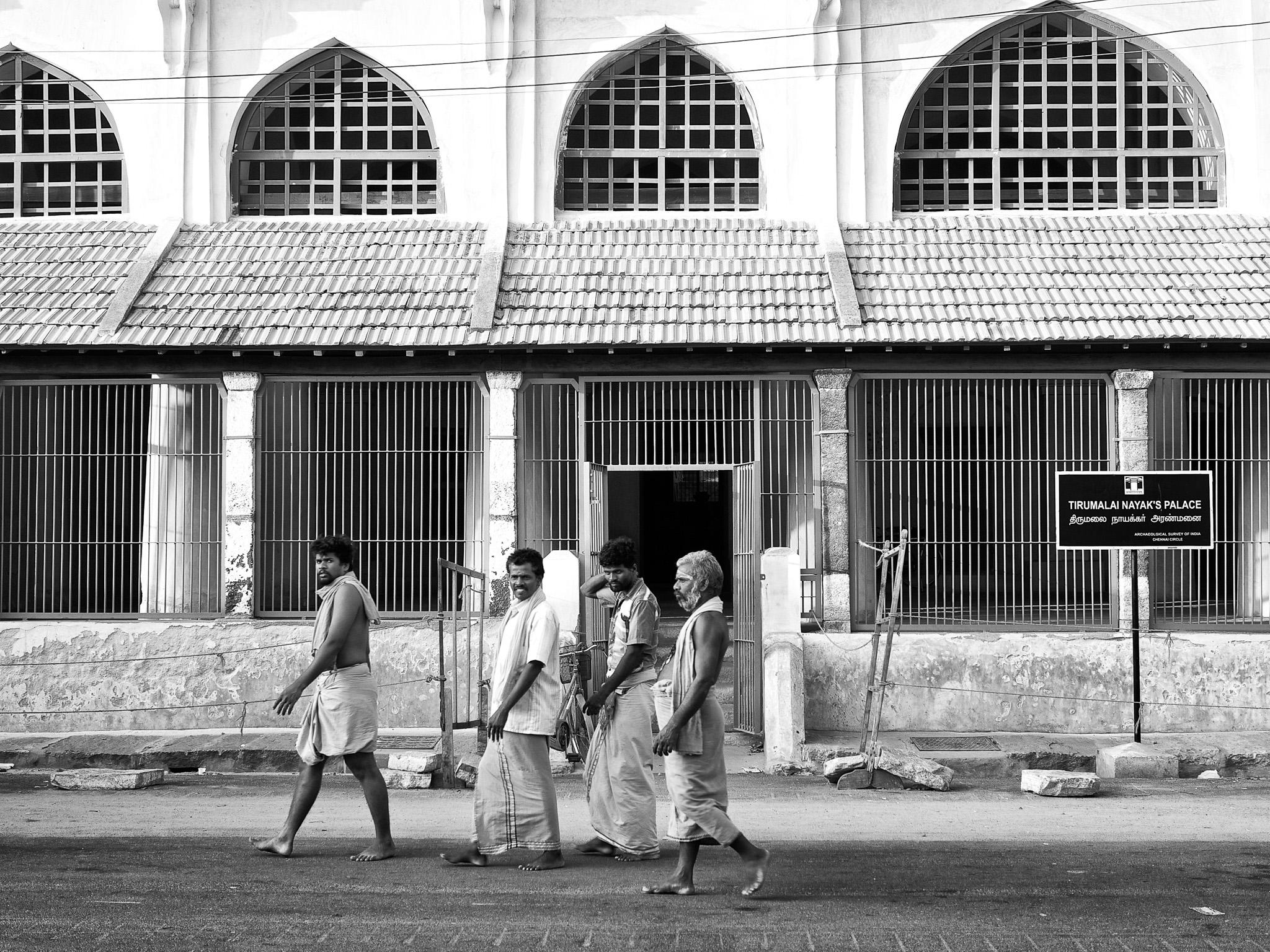 A group of pilgrims walking past a smaller old palace building, Tirumalai Nayak's Palace, at Srivilliputhur, Tamil Nadu, India