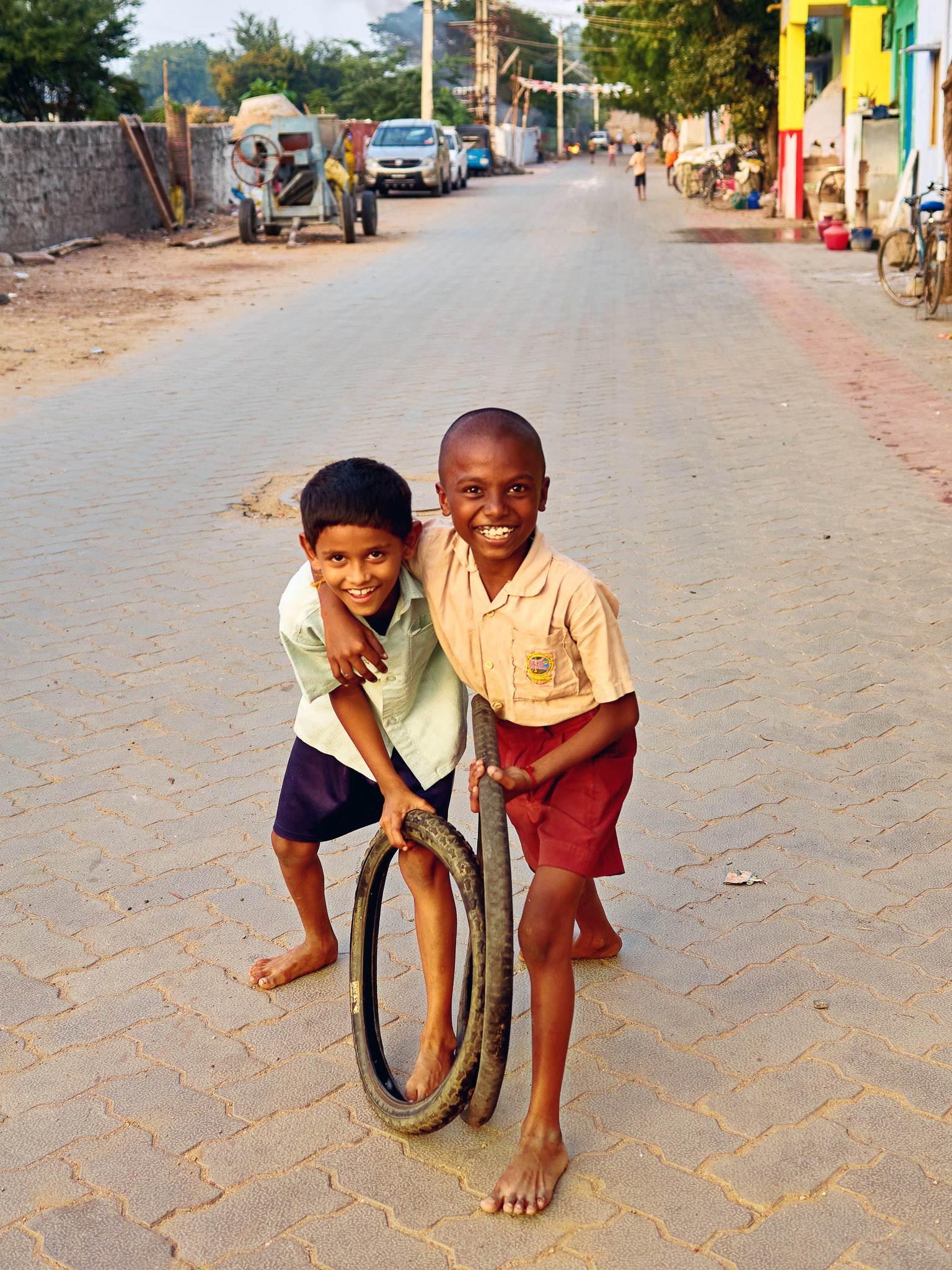 Young boys playing with worn out cycle tyres in the street, Virudhunagar, Tamil Nadu, India