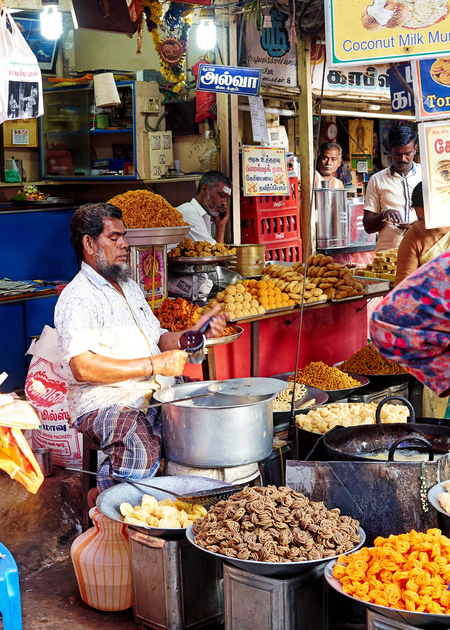 A cook preparing snacks and sweets at the street side shop, Madurai, Tamil Nadu, India