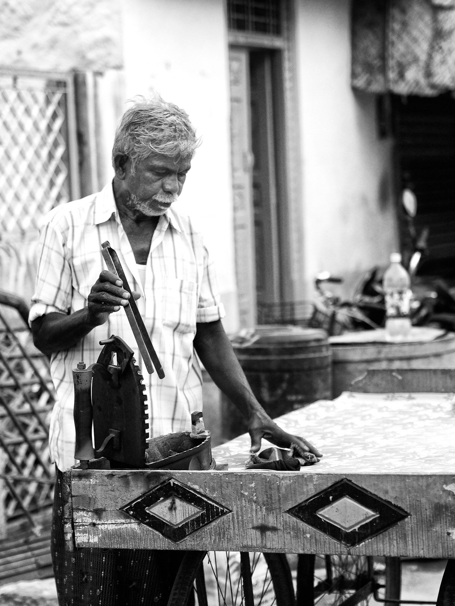 An Ironing man attending hot charcoals with a pincer on his iron box, Virudhunagar, Tamil Nadu, India