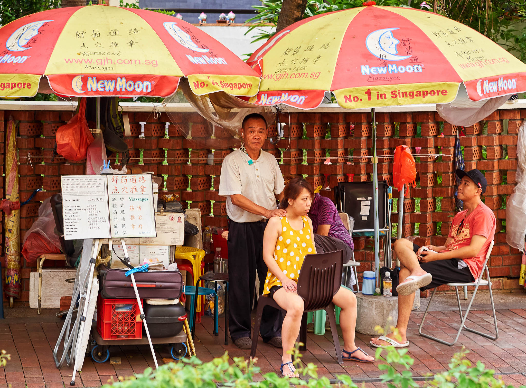 A massage therapist at work in his street-side workplace, Bugis, Singapore