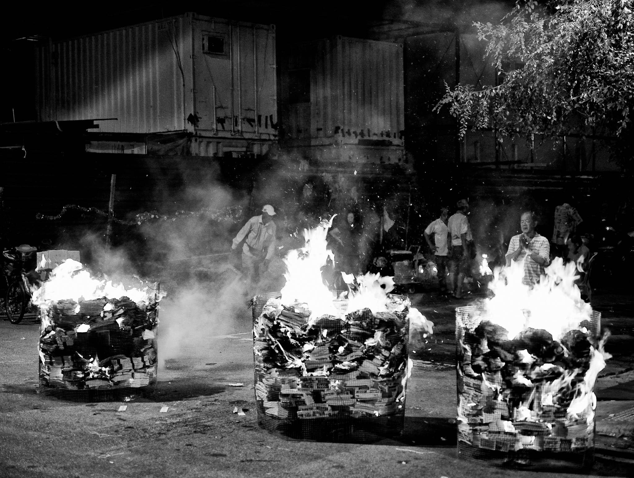 Street vendors offering 7th month prayers after burning up bundles of joss paper, Jln Besar, Singapore