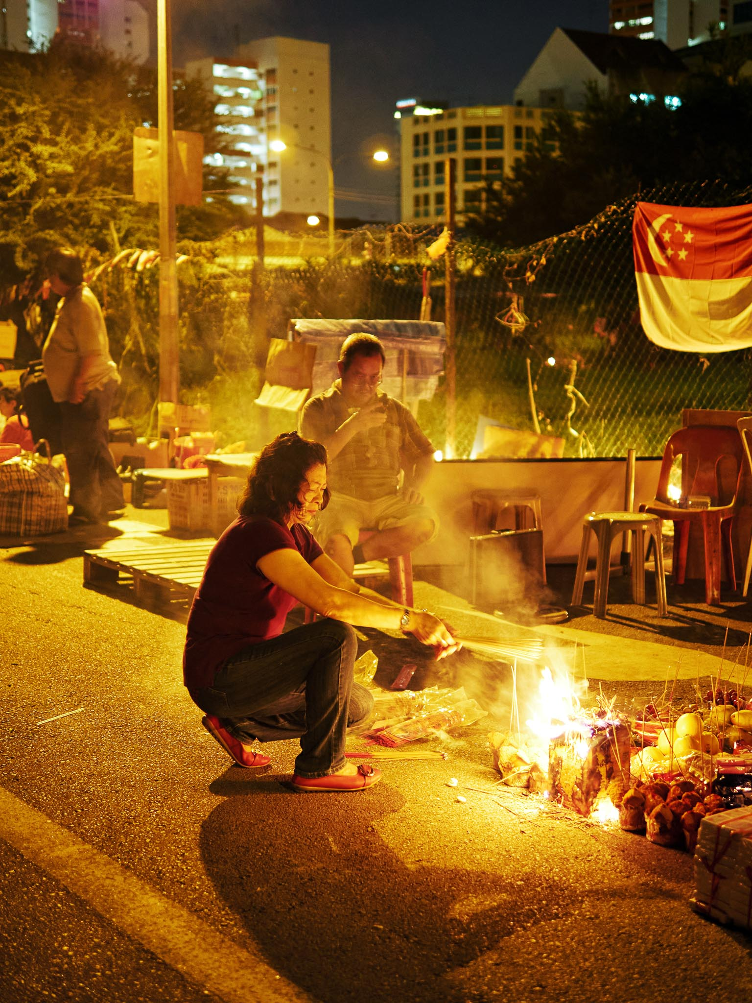 A woman burning incense sticks and joss papers to celebrate the Hungry Ghost (7th month) Festival, Jalan Besar, Singapore