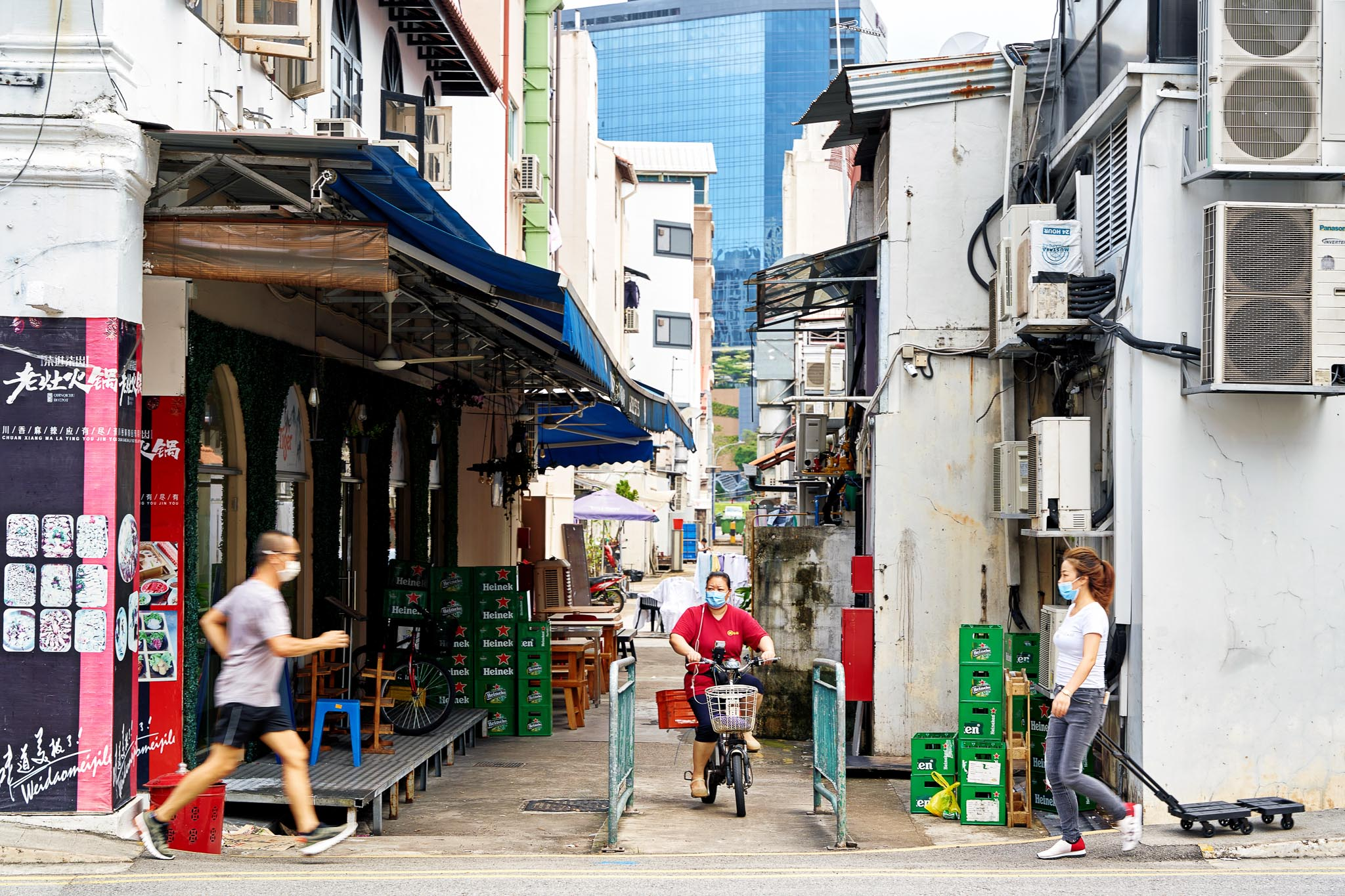 A runner, bicyclist, and a pedestrian converging at an alley, a street scene at Jln Besar, Singapore.