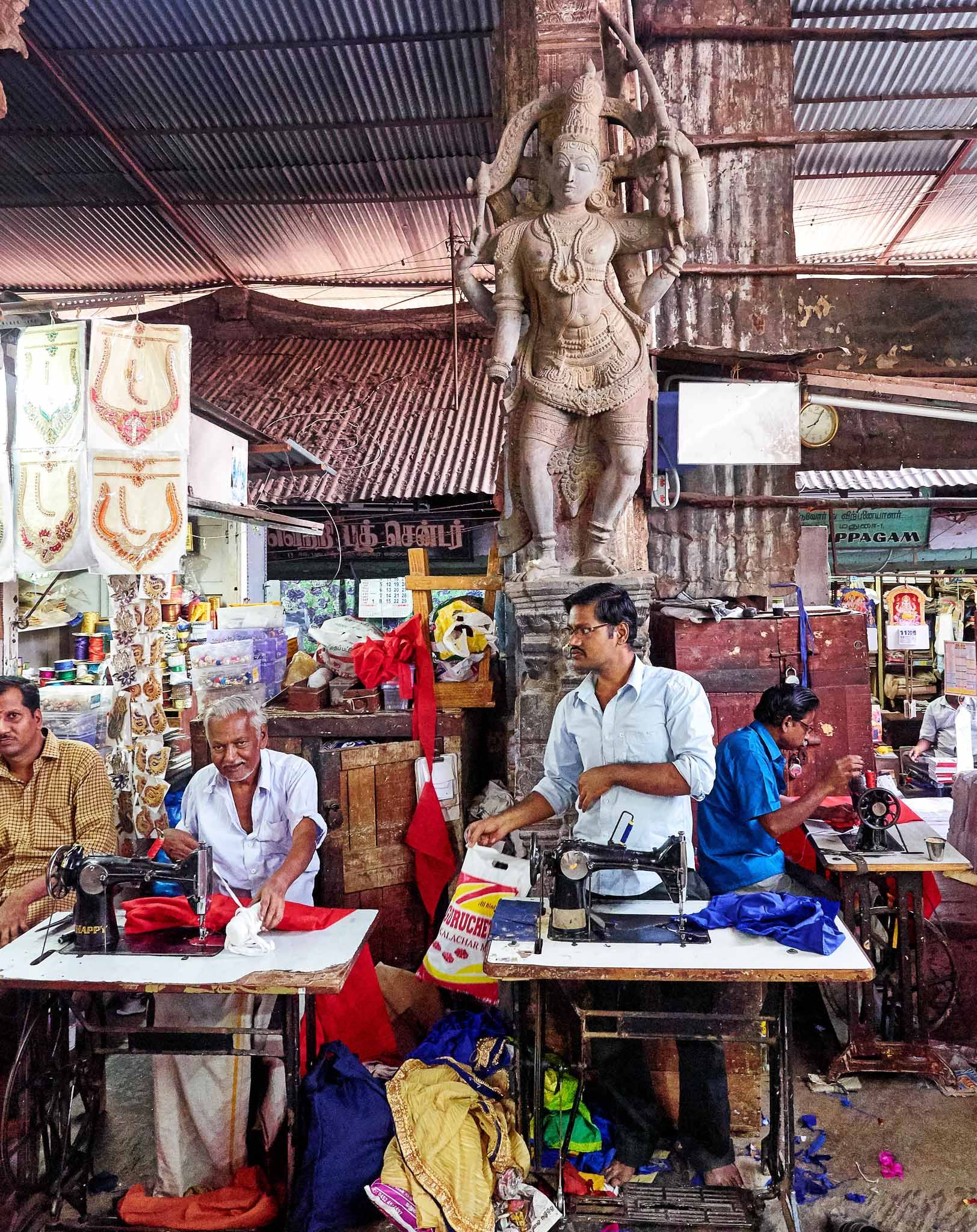 Tailors at work in an old temple hall amidst sculptures, Puthu Mandapam, Madurai, Tamil Nadu, India