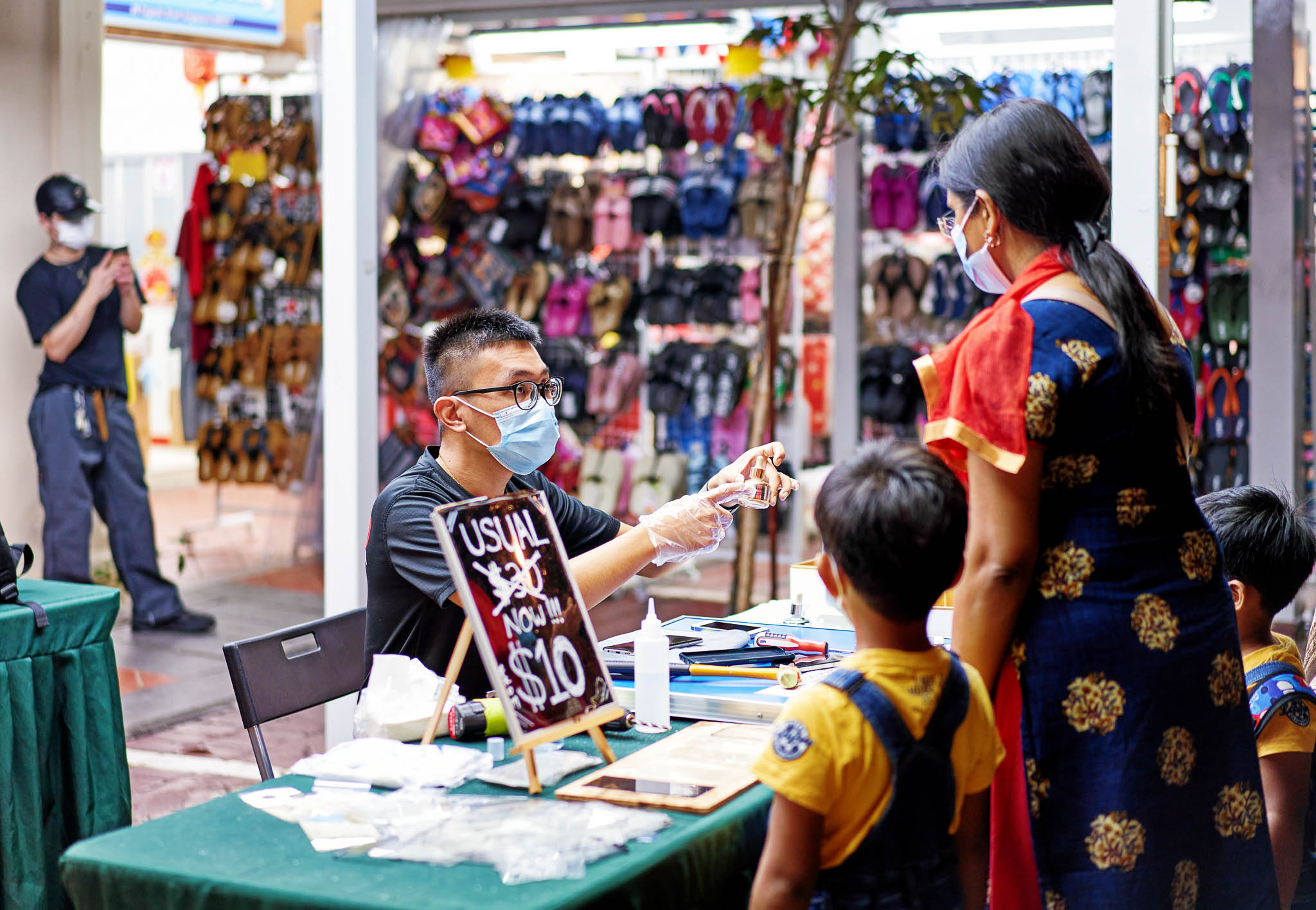 A mobile shop keeper fixing screens for mobile phones attending a customer, Chinatown, Singapore