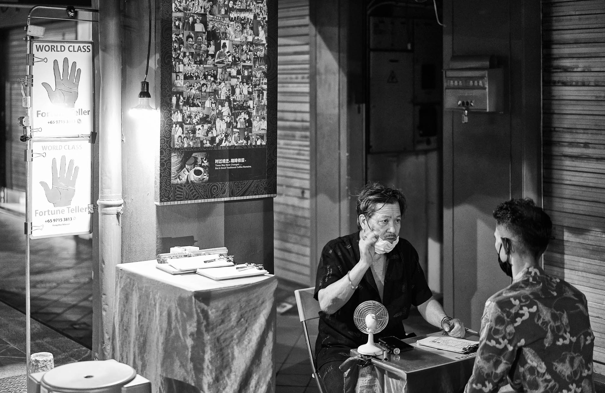 A fortune teller counseling his customer at his roadside stall, Chinatown, Singapore